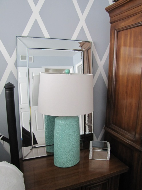 Putting a mirror behind a lamp will help bounce light around a room.